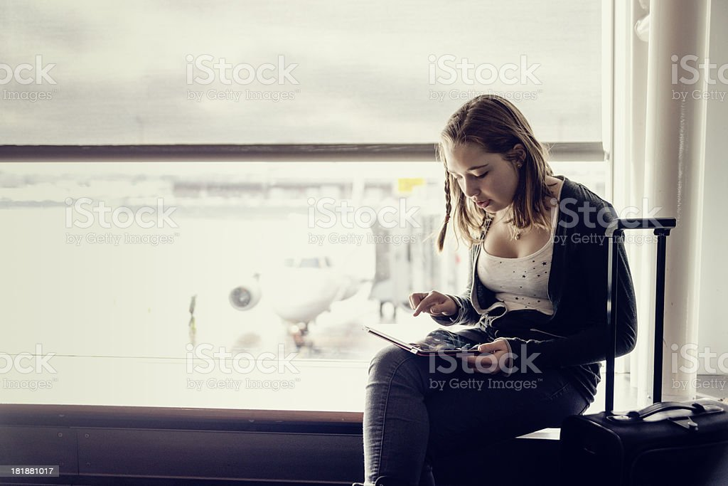 Travelling girl waiting in airport with digital tablet, copyspace. royalty-free stock photo