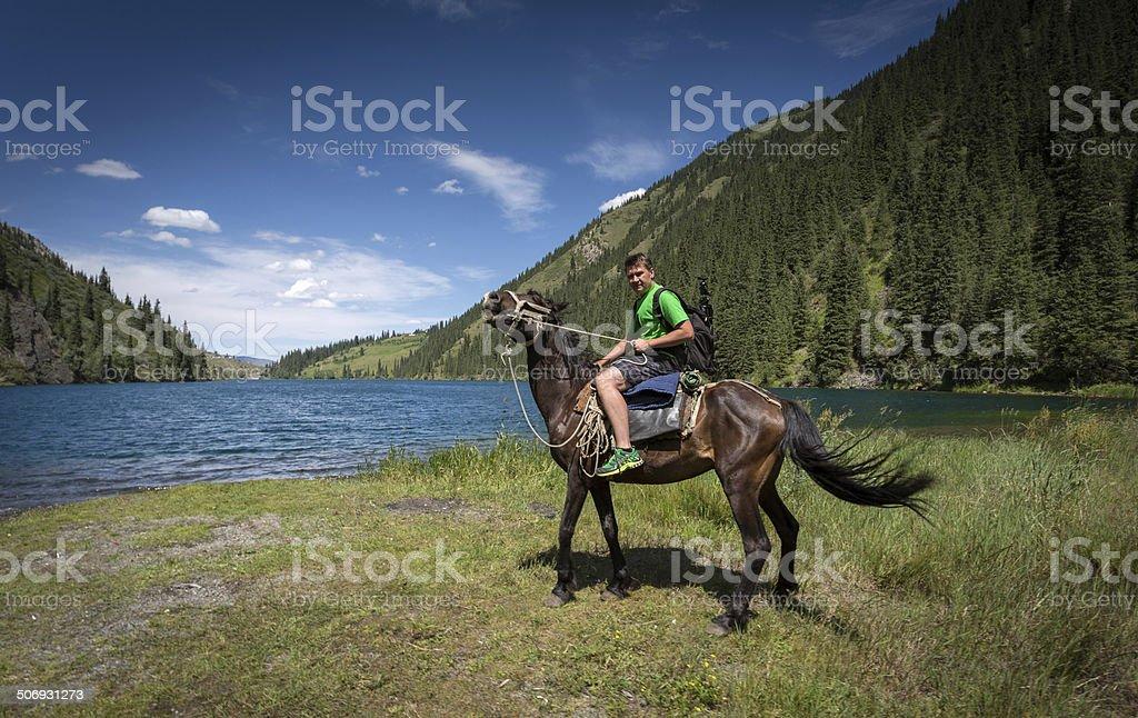 Travelling on horseback on a mountain lake stock photo