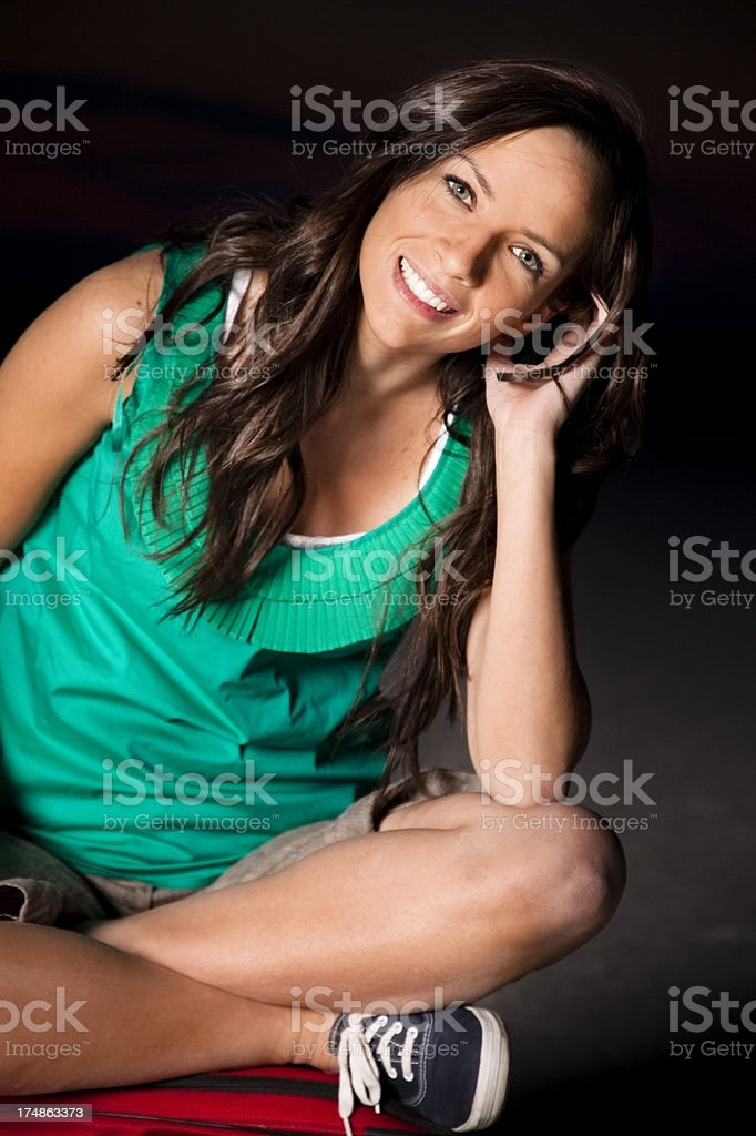 Travels:  Young adult Caucasian female sitting on suitcase at dusk. royalty-free stock photo