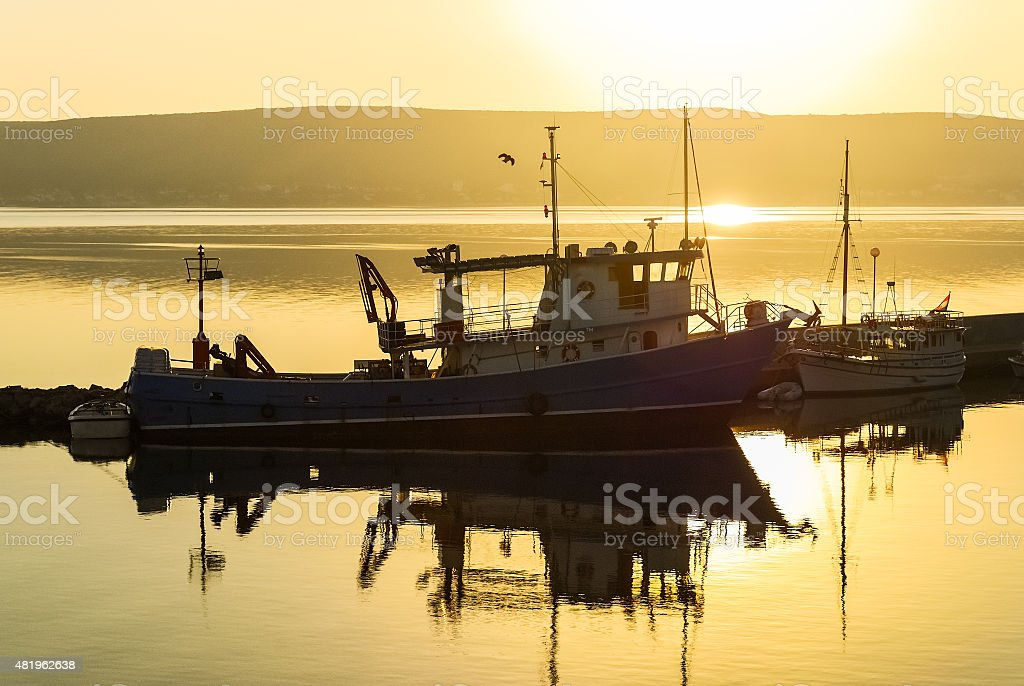 Trawler in the harbor at sunrise stock photo