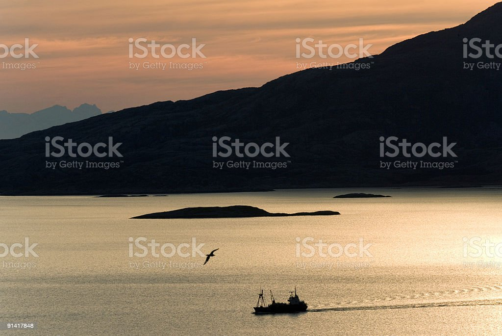 Trawler silhouette on Norwegian Fjord at sunset royalty-free stock photo