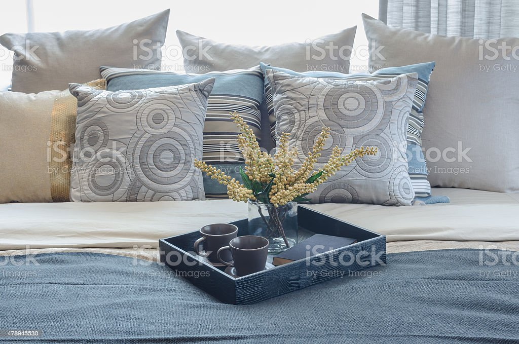 tray of cup and glass vase of plant on bed stock photo