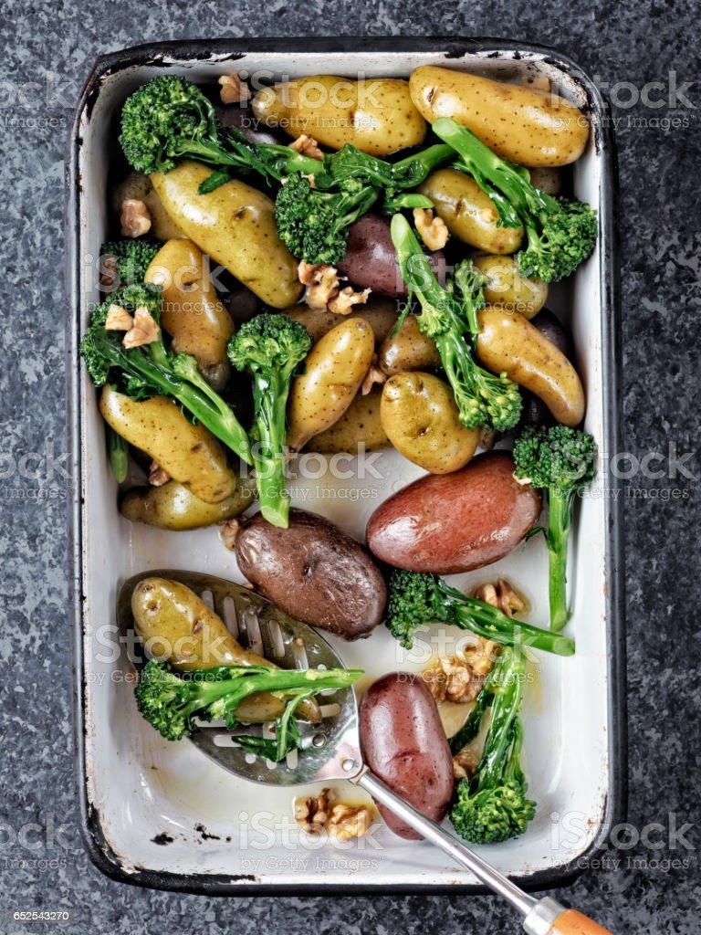 tray of potato broccolini salad stock photo