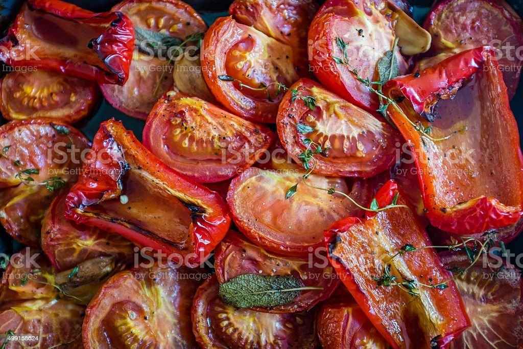 Tray of roasted red peppers and tomatoes stock photo