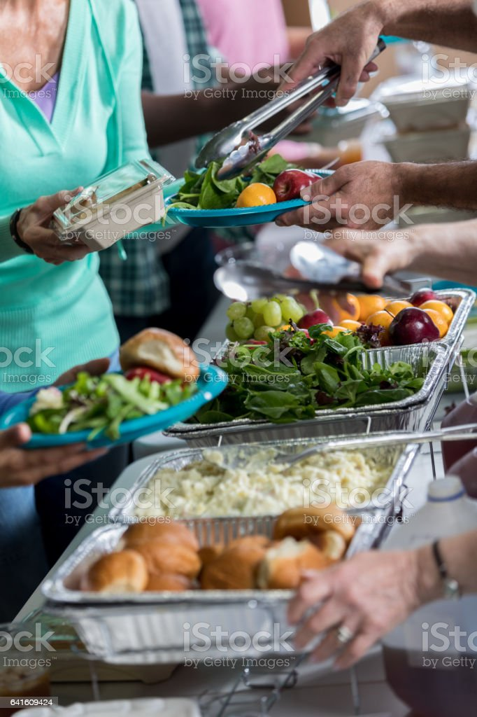 Trays of healthy food are served in soup kitchen stock photo