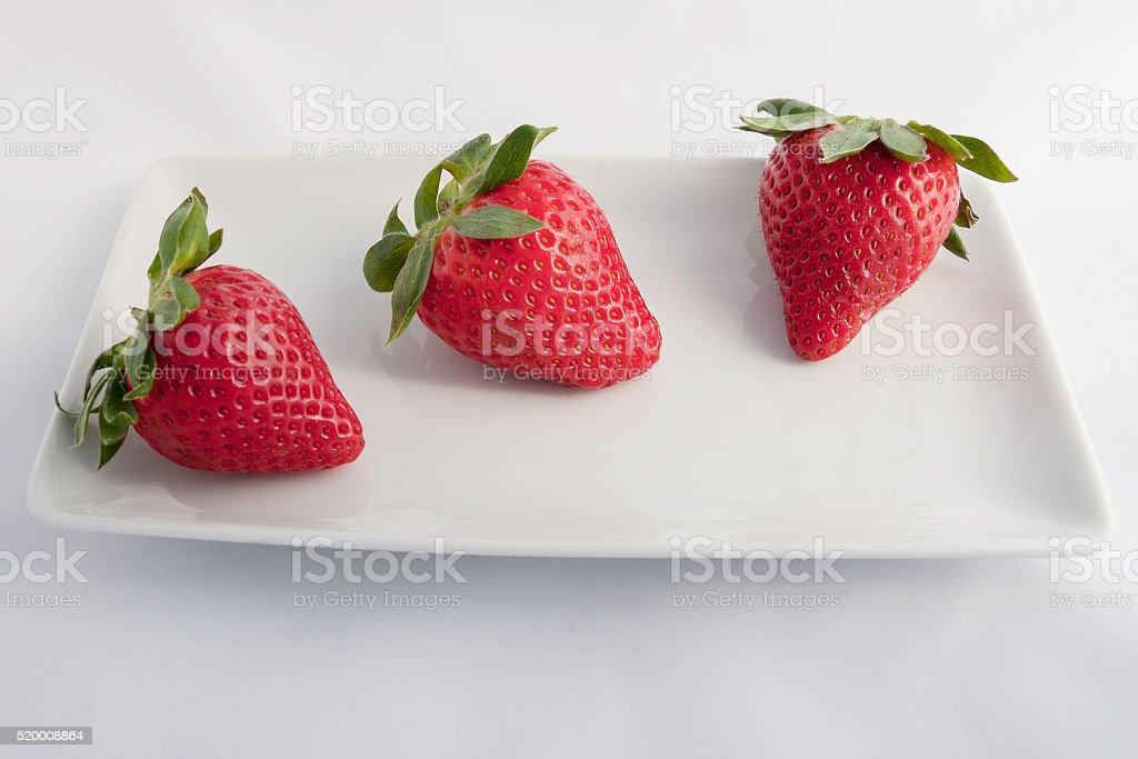 tre fragole disposte  sopra un piattino bianco stock photo