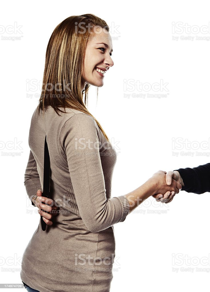 Treachery! Insincerely smiling beauty with backstabbing knife behind back stock photo