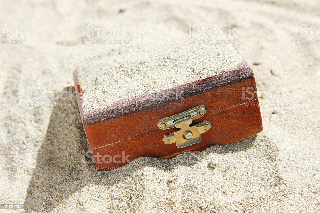 Treasure Chest Buried in Sand stock photo