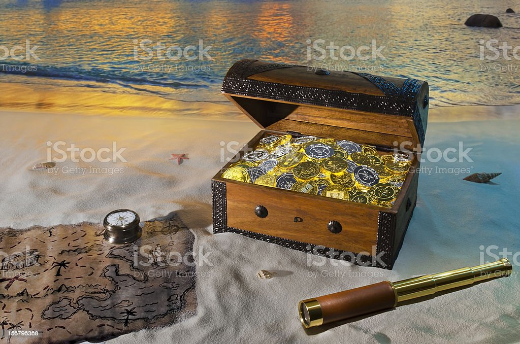 Treasure chest with gold coins on a beach stock photo