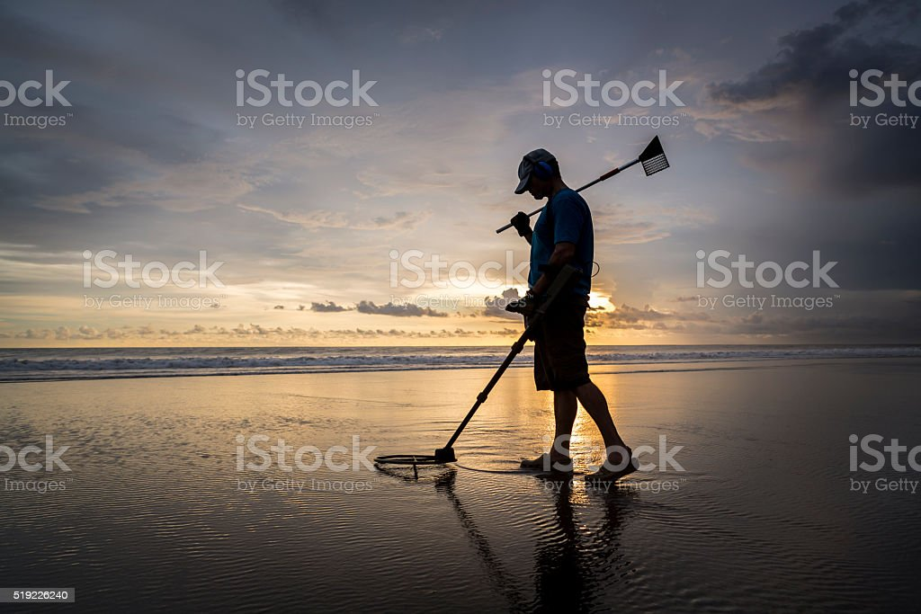 Treasure hunter on the beach with a metal detector stock photo