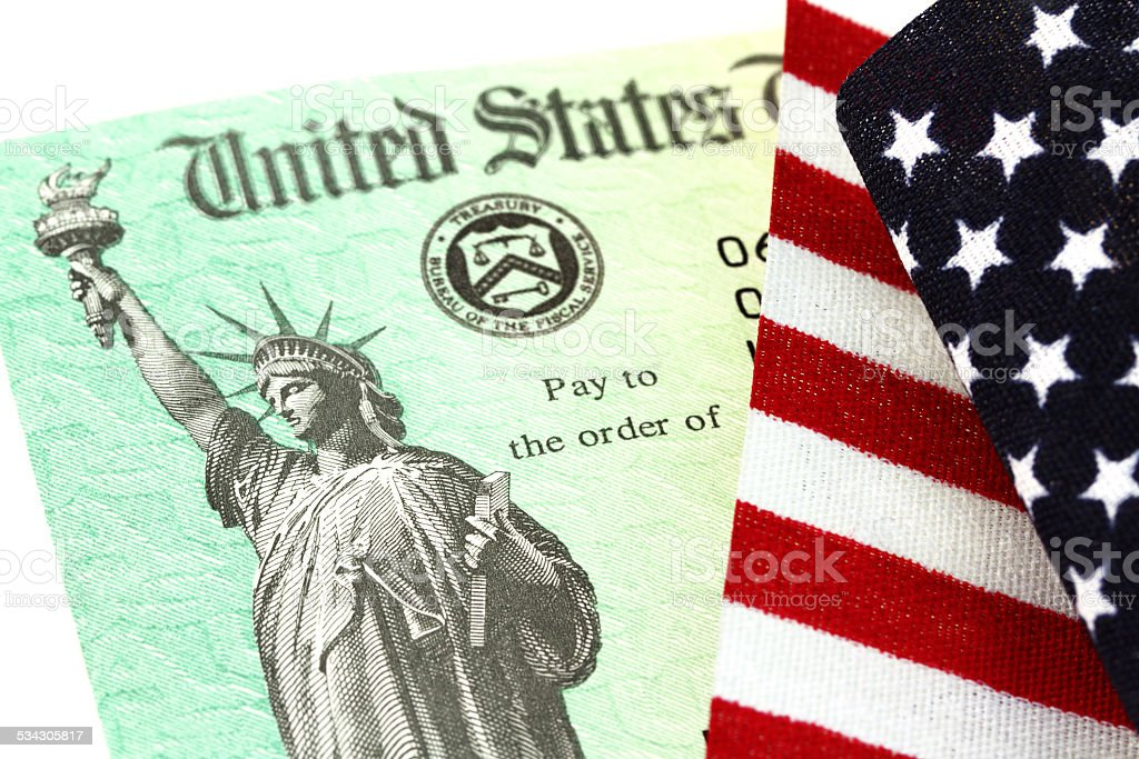 USA Treasury IRS refund check on American flag stock photo