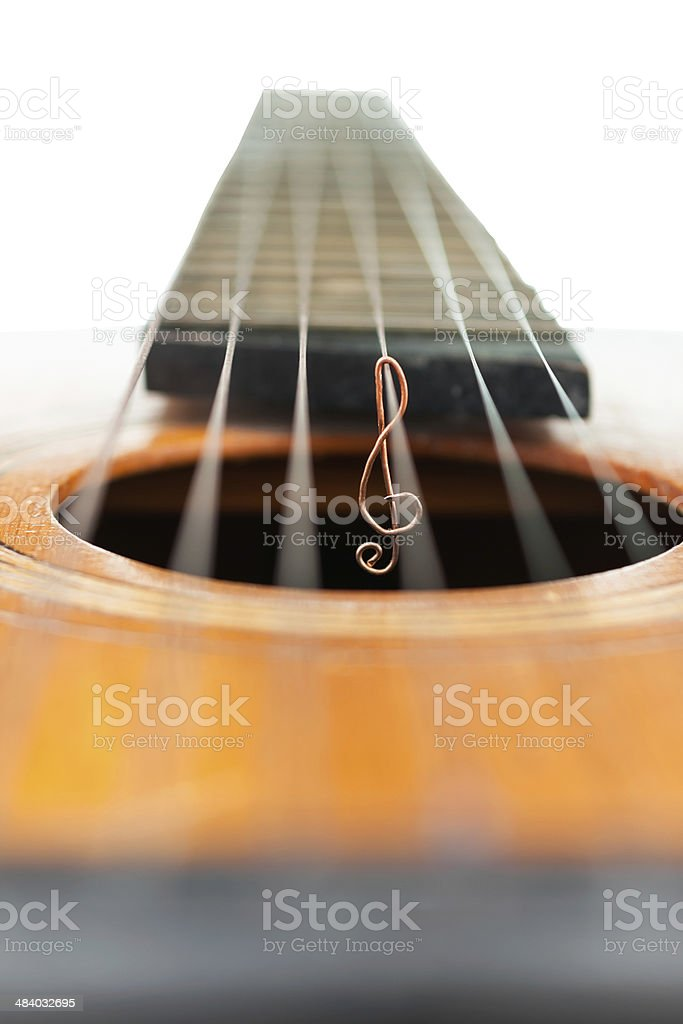 Treble clef on the strings of a guitar stock photo