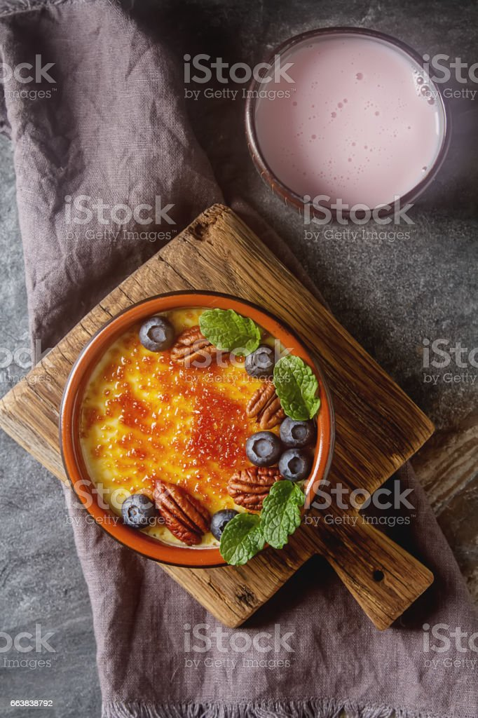 Treditsiozny French dessert. Homemade Creme brulee caramel with nuts and berries, mint. Dark background. stock photo