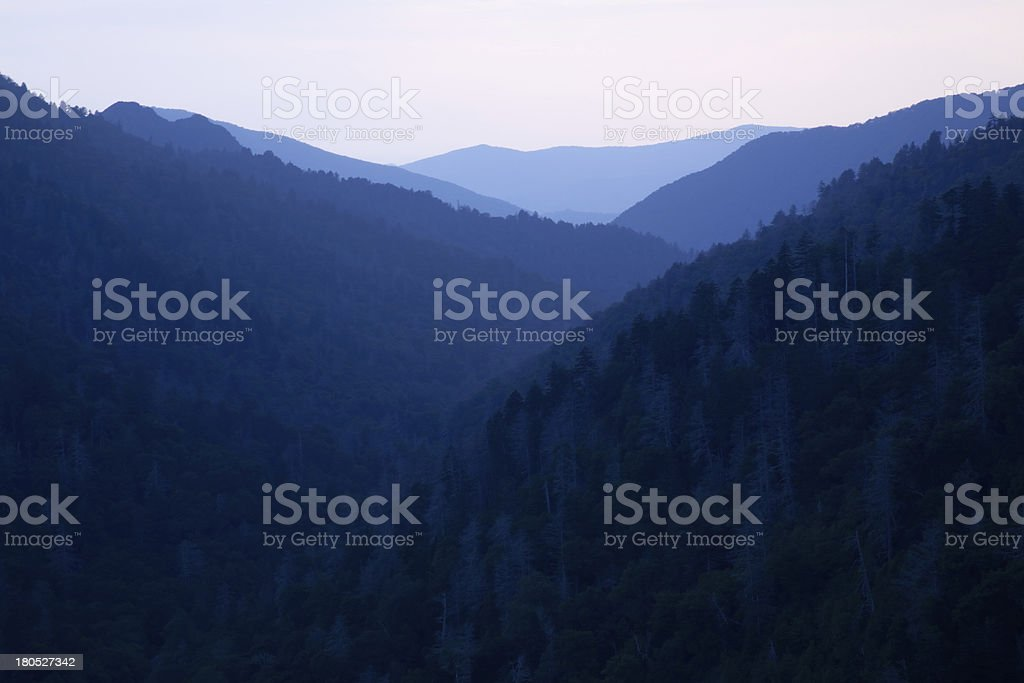 Tree covered mountains and a cloudy sky at sunset royalty-free stock photo