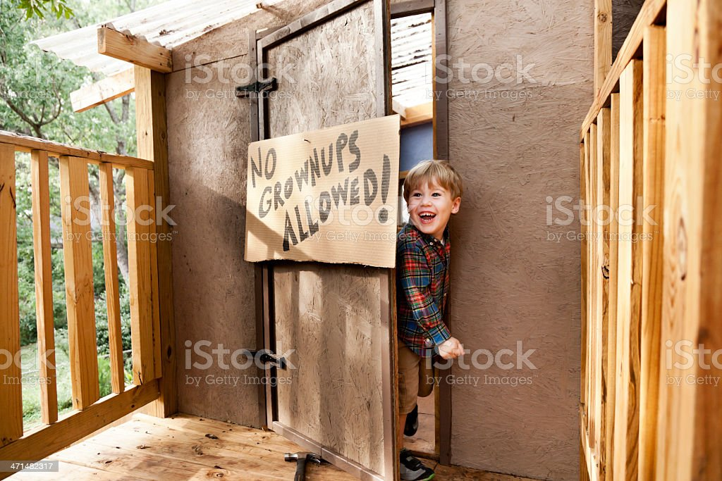 A tree house with a little boy opening the door stock photo