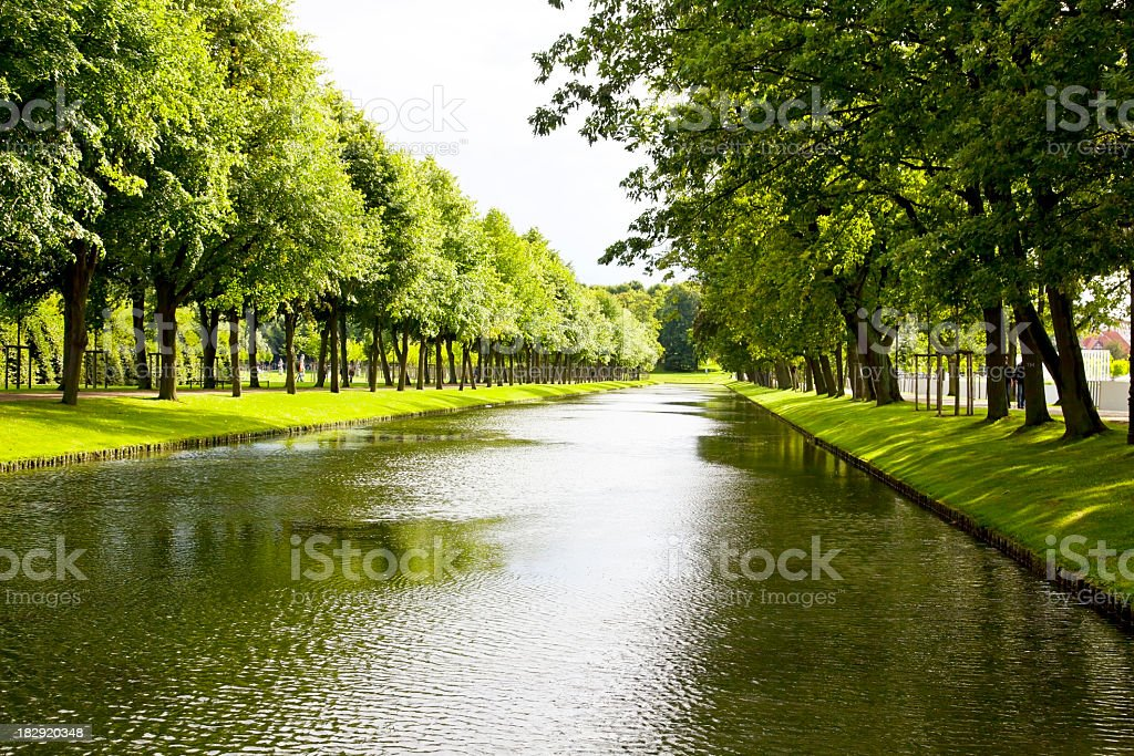 Tree lined canal in a lush green park stock photo