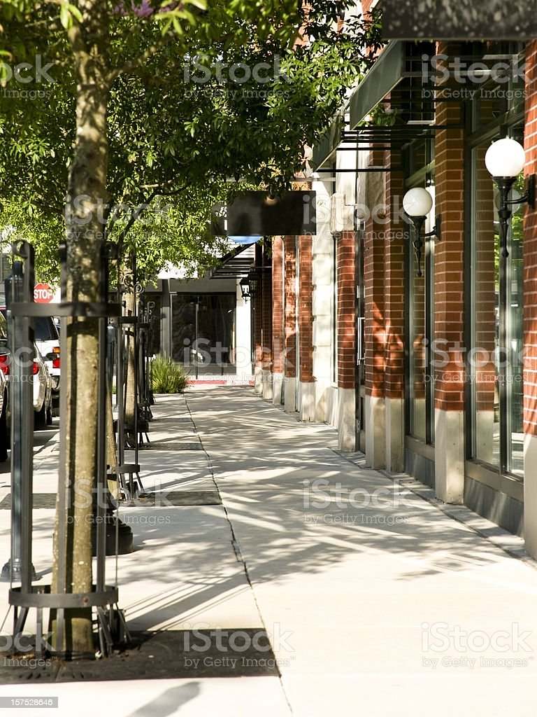 Tree lined sidewalk in front of main street shops. Downtown. stock photo