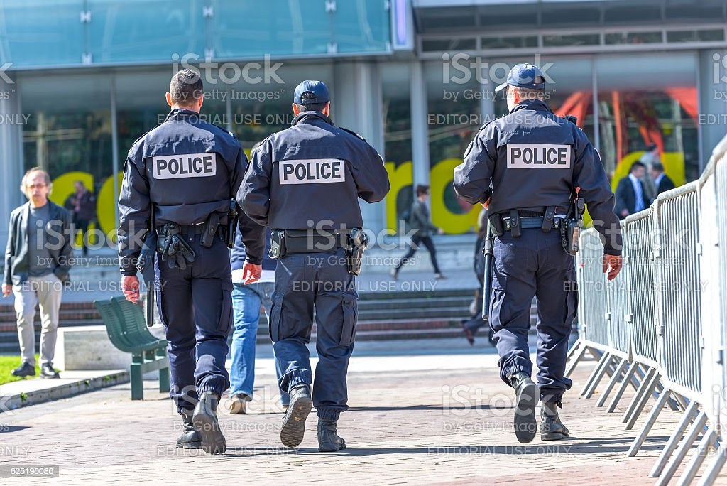 tree police officers walking in the street stock photo