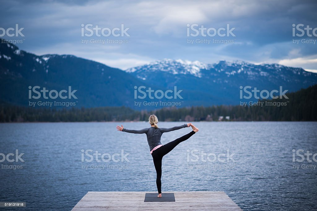 Tree pose lakeside yoga stock photo