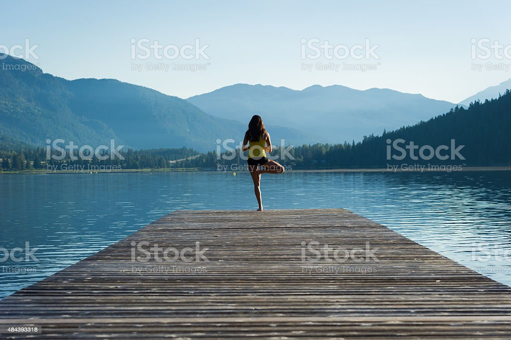 Tree Pose Tranquil Lakeside meditation at sunrise stock photo