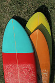 Tree surfboard on each other in different shapes and colors