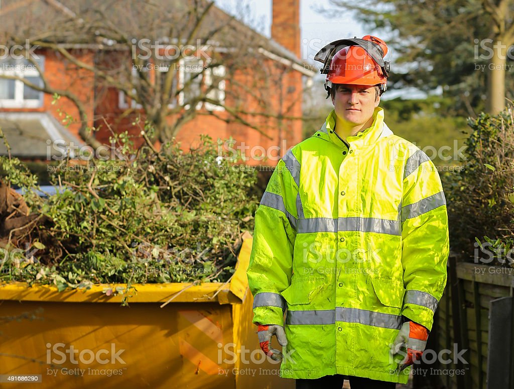 Tree surgeon in front of skip full of tree cuttings stock photo