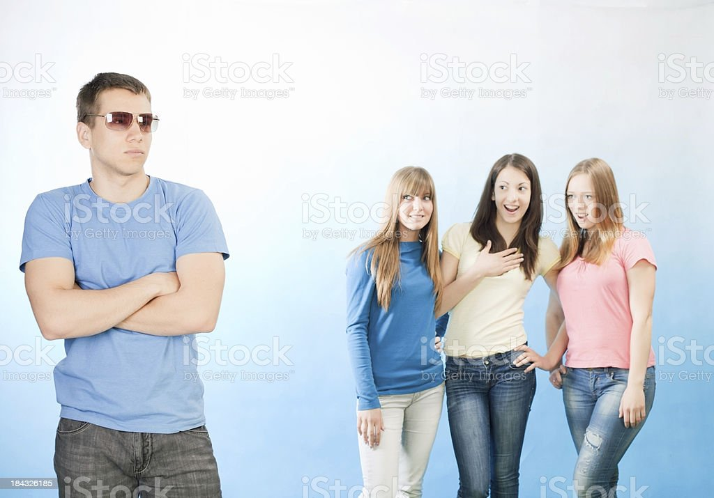 Tree teenage girls looking at popular handsome guy royalty-free stock photo