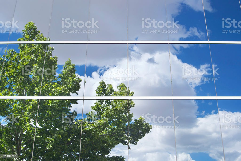 tree with cloud filled sky reflected in office building glass royalty-free stock photo