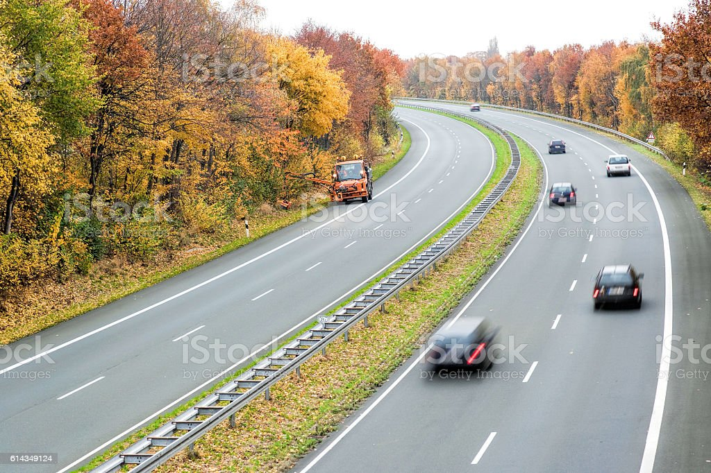 Treelined highway with blurred cars in autumn stock photo