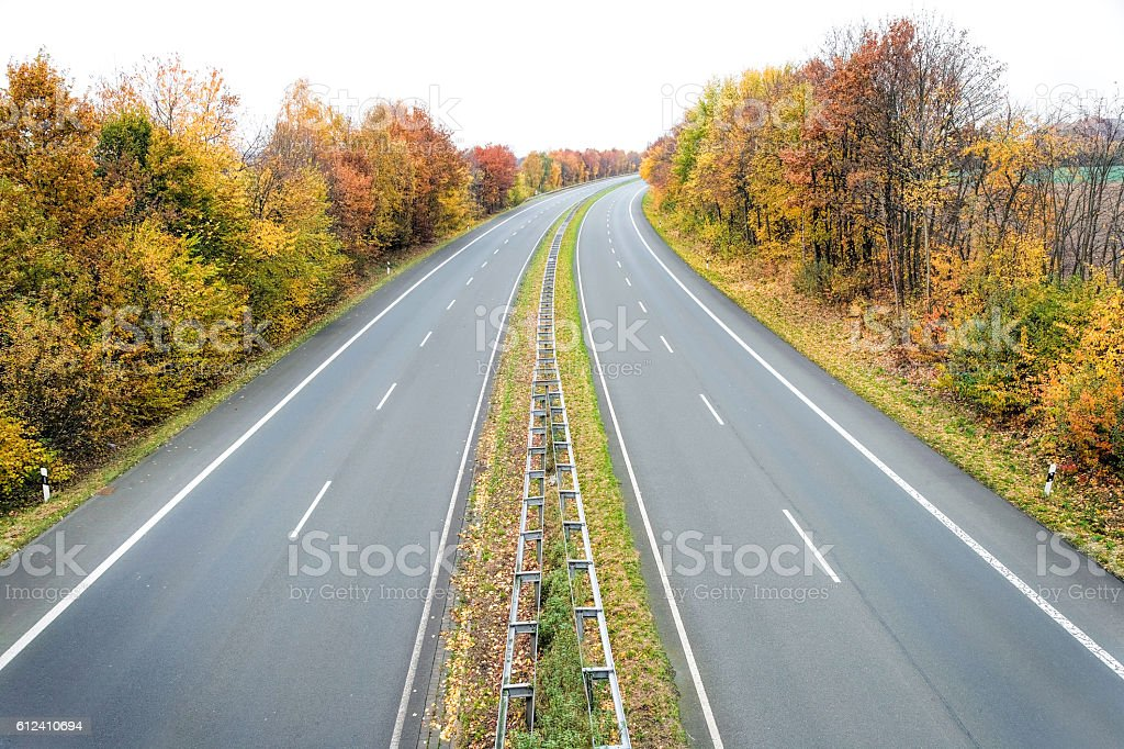 Treelined two lane highway in autumn stock photo