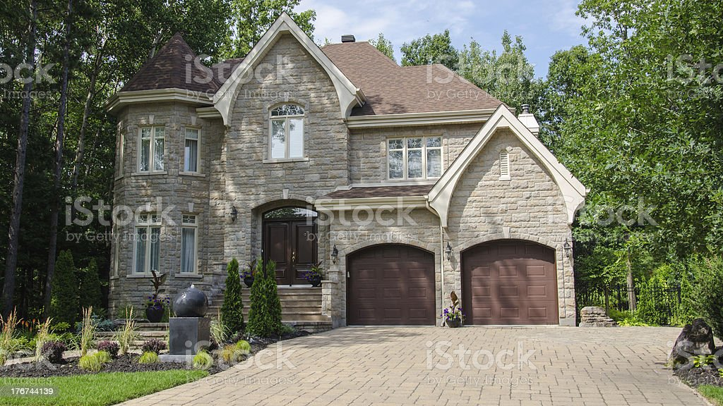 Trees behind a large beige stone house with two garages royalty-free stock photo