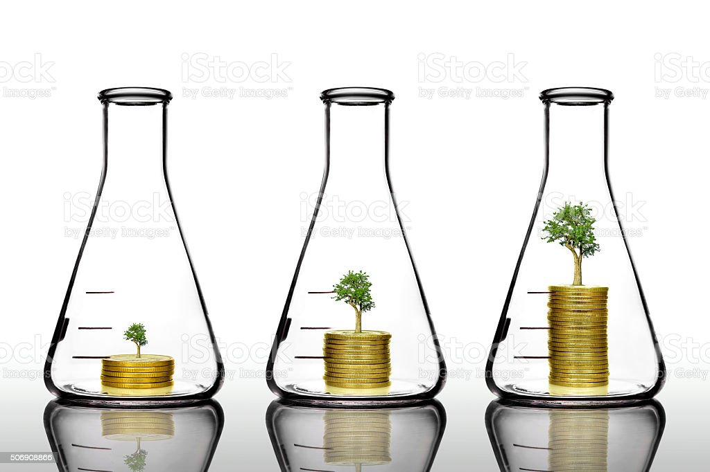 trees growing on golden coins in clear flask stock photo