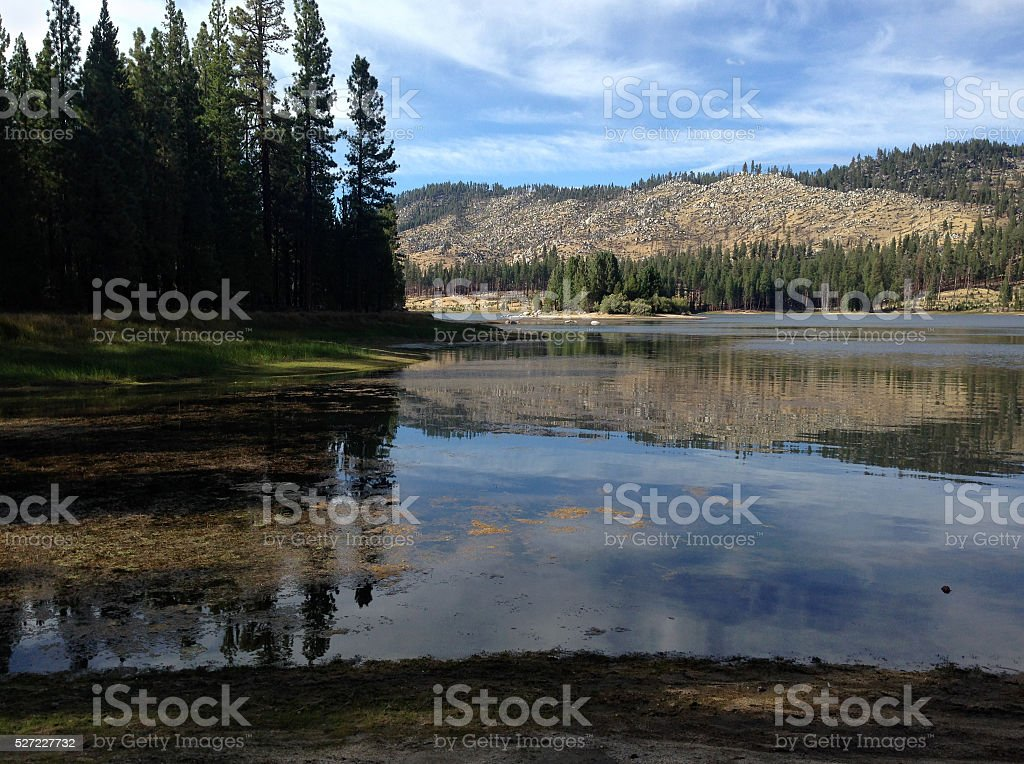 Trees, Mountains and Clouds Reflecting in a Lake royalty-free stock photo