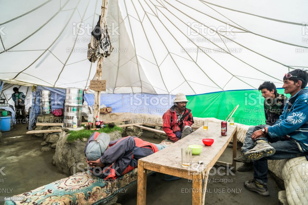 Trek guides resting in the restaurant tent at Nemaling, Markha valley stock photo