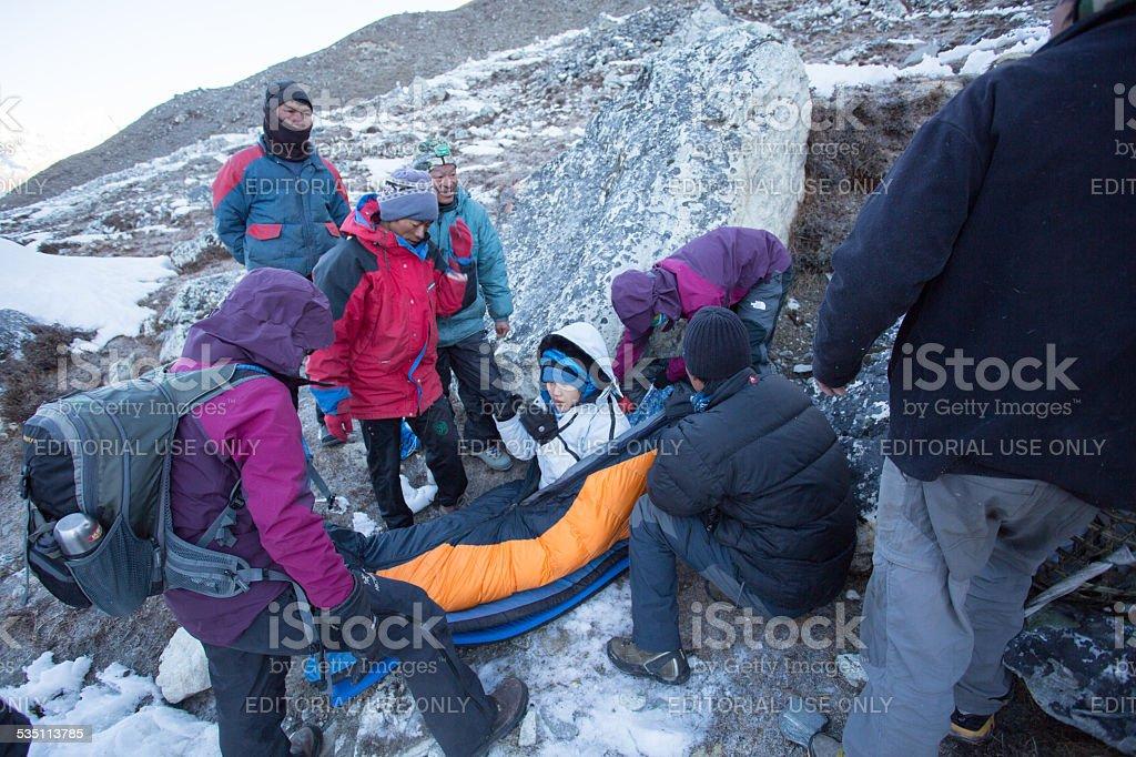trekker broken leg rest and wait for  helicopter stock photo