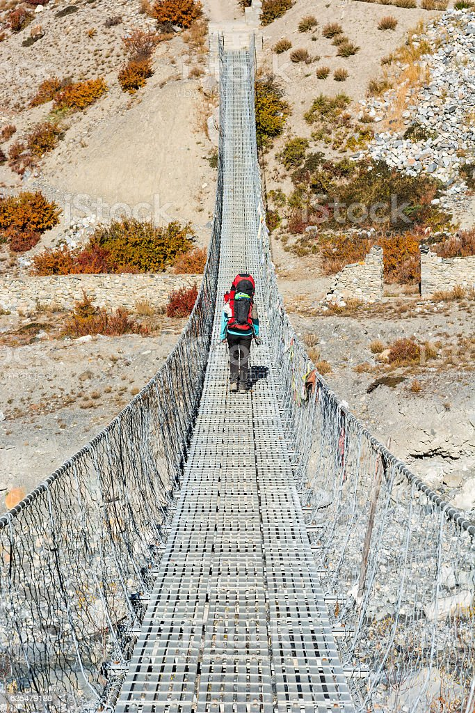 Trekker crossing metal suspension bridge. stock photo