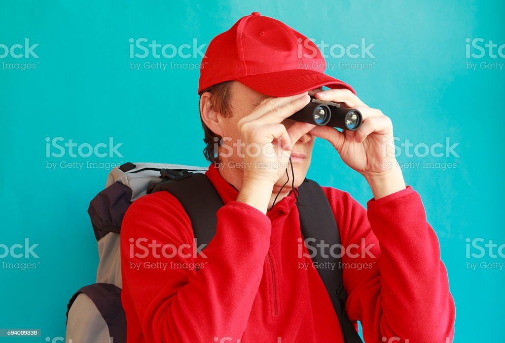 trekker during an excursion looking through his binoculars stock photo