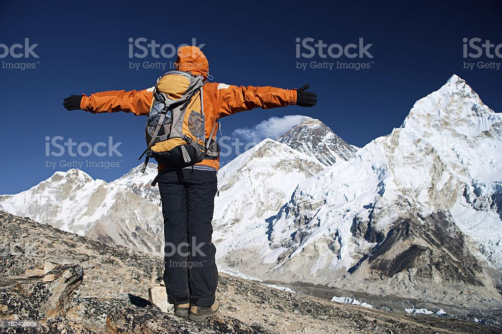 Trekker lifts her arms in victory, Mount Everest on background royalty-free stock photo