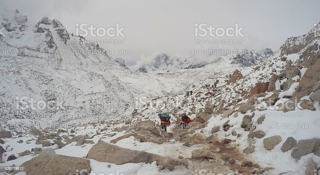 Trekkers and porters in mountains stock photo