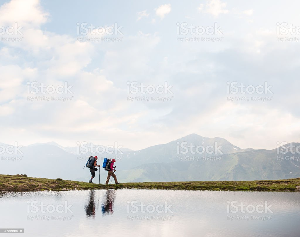 Trekkers walking along a clear lake in the mountains stock photo