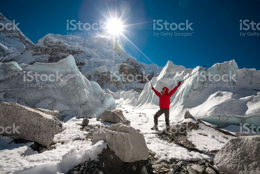 Trekkes is posing at camera in front of huge glacier falling from Everest close to Everest base camp stock photo