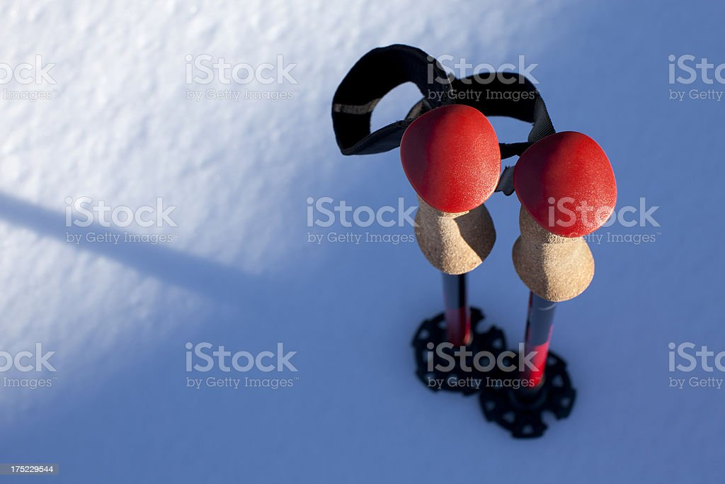 Trekking poles in the snow stock photo