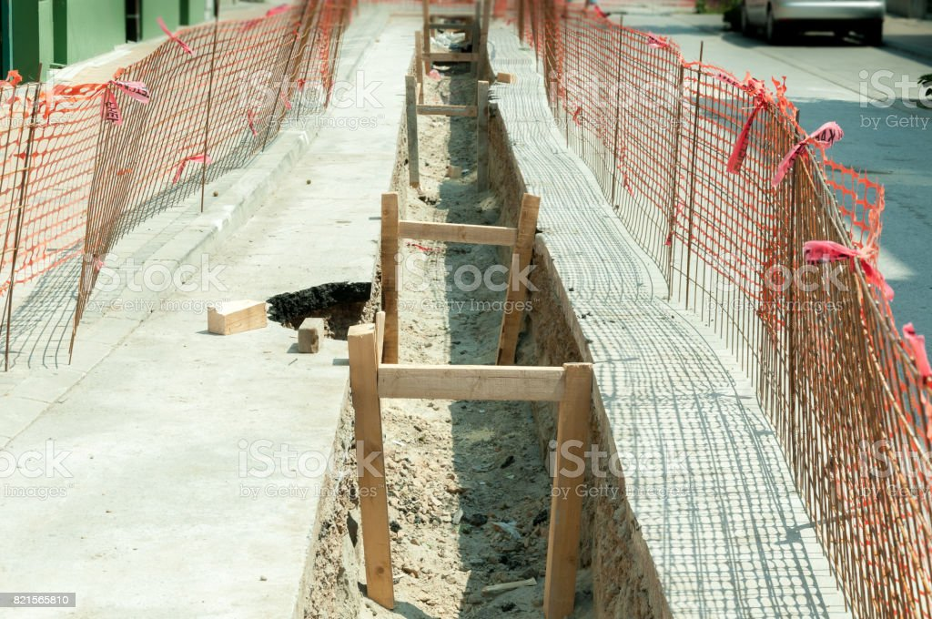 Trench for district heating pipeline reinforced with wooden beams and fenced with construction site safety net. stock photo