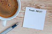 Trends 2017 written at notepad on table workplace near cup