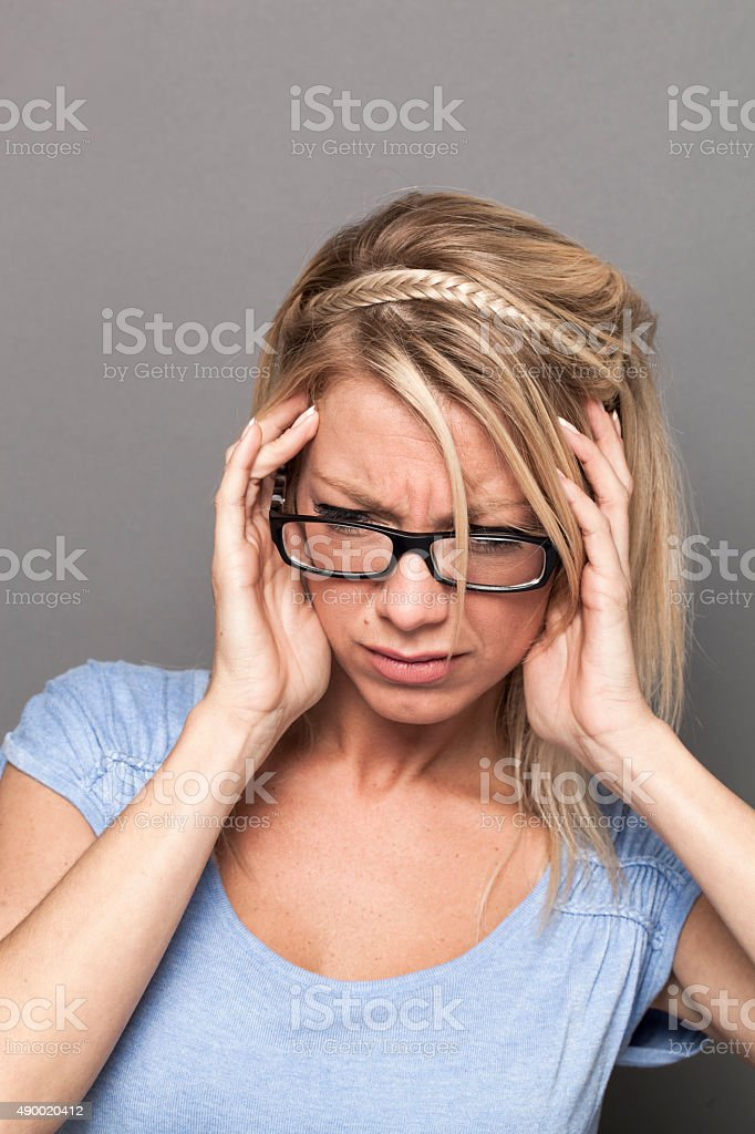 trendy 20s blond girl in pain having migraine or tinnitus stock photo