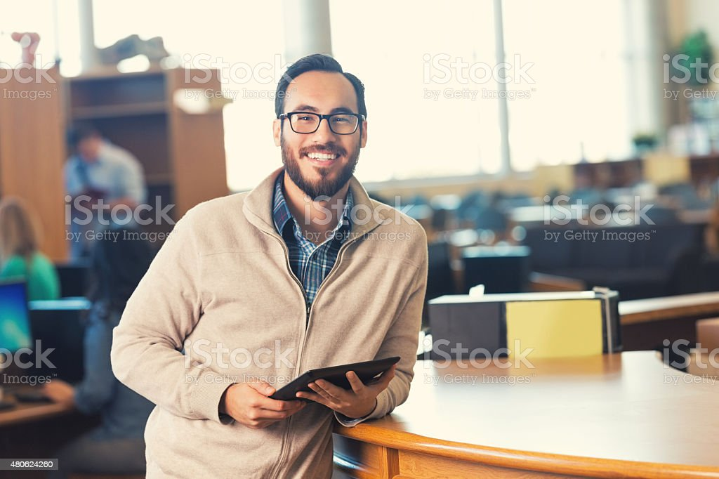 Trendy adult college student in library with digital tablet stock photo