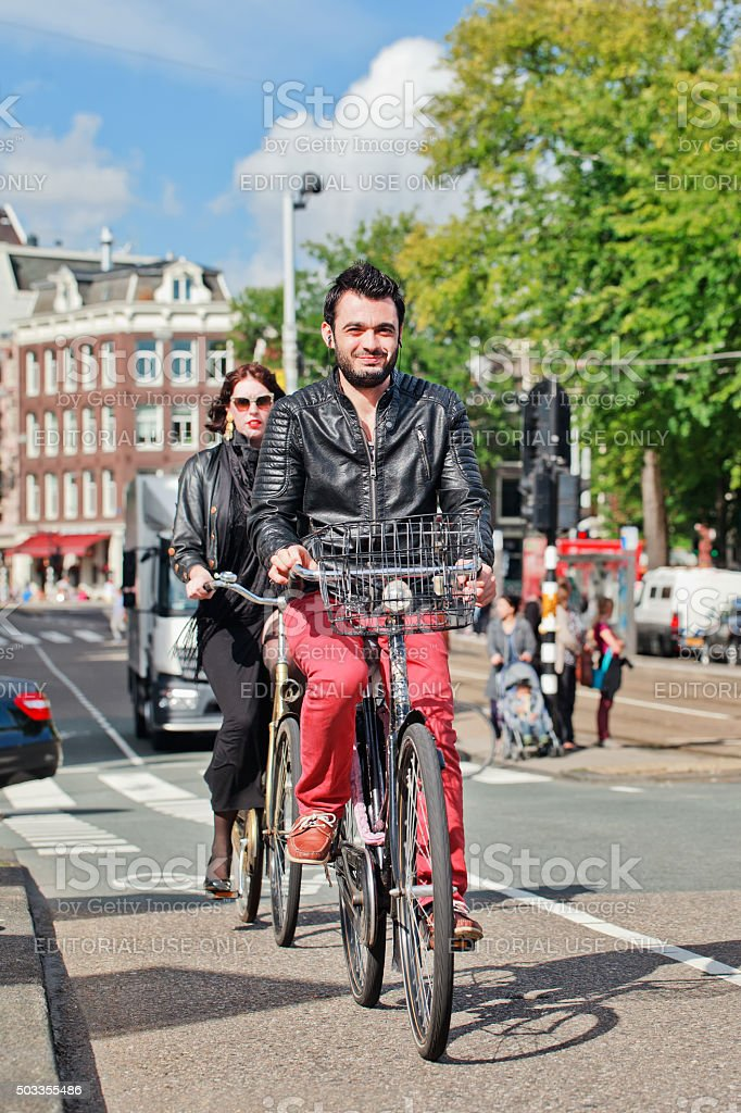 Trendy Amsterdam citizens cycling in a sunny city center stock photo