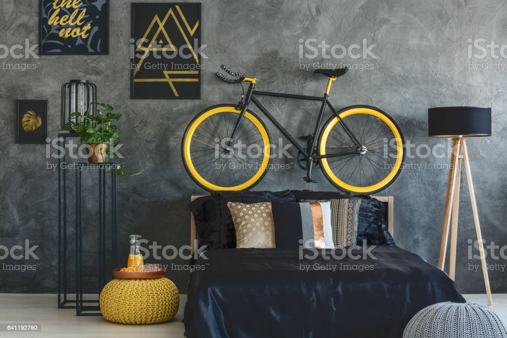 Trendy grey bedroom with bed, bike and wall posters