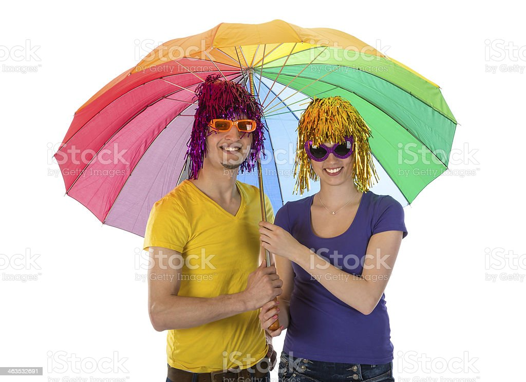 Trendy couple with sunglasses and wigs under a rainbow unbrella stock photo