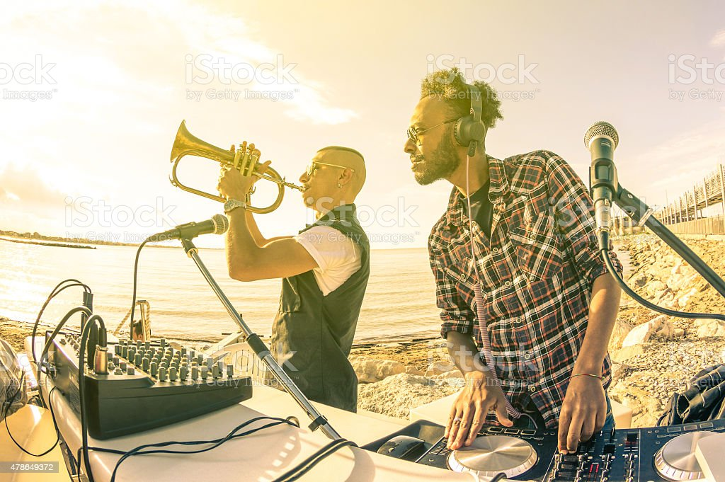 Trendy djs playing summer hits at sunset beach party stock photo